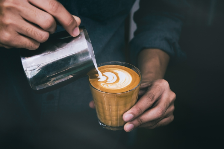 Close-up of male barista hand holding and pouring hot milk for prepare latte art on piccolo latte cup of coffee.